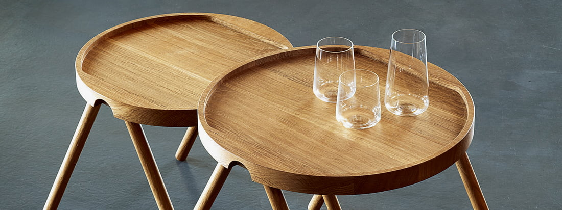 The design brand Auerberg produces high quality products - like the Tray Table made of wood. Thanks to a border glasses can be put down the table without any problems.